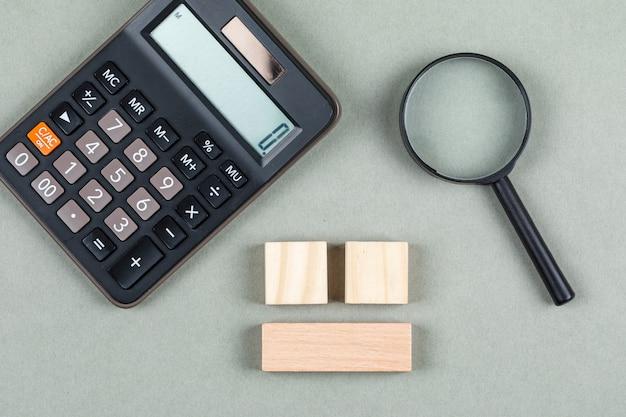 Концепция финансового анализа и бухгалтерии с увеличителем, деревянными блоками, калькулятором на сером взгляд сверху предпосылки. горизонтальное изображение Бесплатные Фотографии