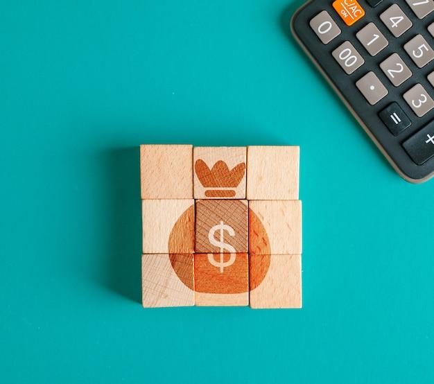 나무 조각에 아이콘으로 금융 개념, 청록색 테이블 평면에 계산기 누워. 무료 사진