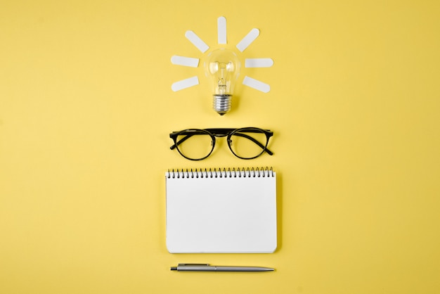 Financial planning table top with pen, notepad, eyeglasses and light bulb on yellow background. Premium Photo