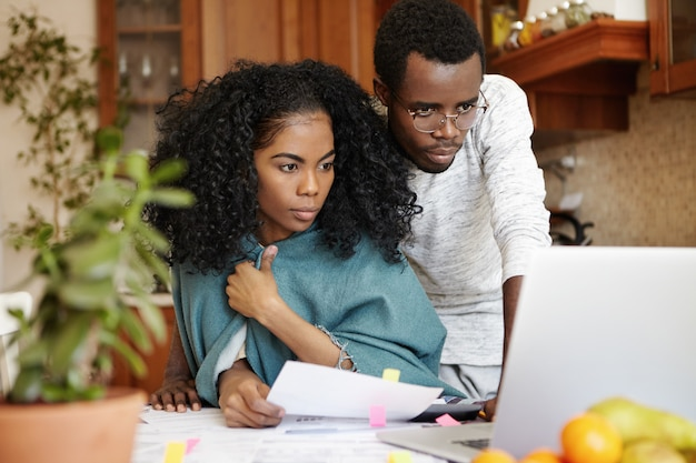 Financial problems, family budget and debts. frustrated young african husband and wife using laptop pc while doing paperwork together, calculating expenses, managing bills in their modern kitchen Free Photo