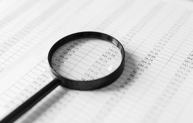 Financial reports and a magnifying glass with on table office. Premium Photo