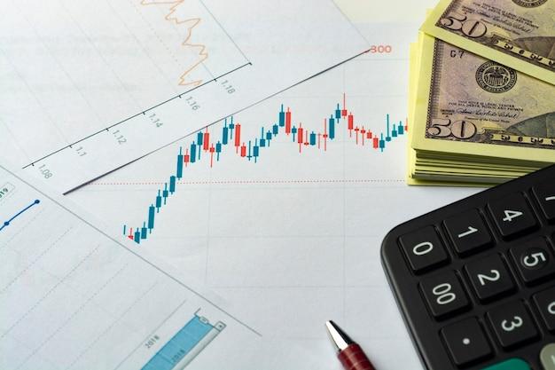 Финансовые отчеты. бизнес-график. ручка и калькулятор с долларовыми банкнотами на финансовом графике или данных фондового рынка. Premium Фотографии