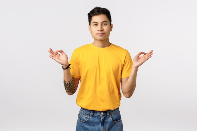 Find peace inside your sould. calm and relieved, peaceful young handsome tattooed asian guy meditating, release stress, spread hands sideways with zen orbs, reach nirvana, feel patience Premium Photo