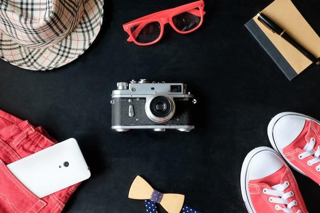 Набор старинных пленочных фотографий fineart: красные кроссовки, красные очки, красные джинсы, винтажная камера, белый телефон, блокнот, стилус, клетчатая шапка и бабочка Premium Фотографии