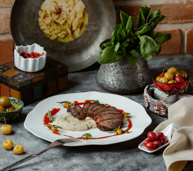 Finely cut beef steak served with rice garnish and tomato sauce Free Photo