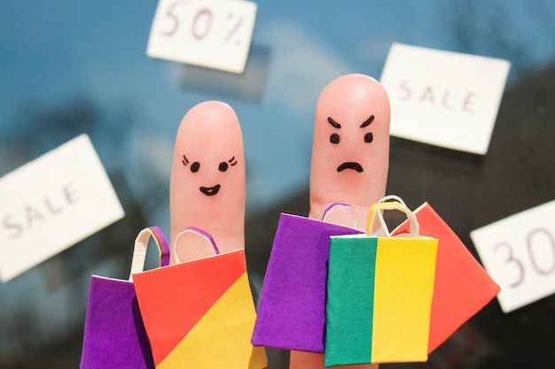 Finger art of couple with shopping bags. man is unhappy Premium Photo