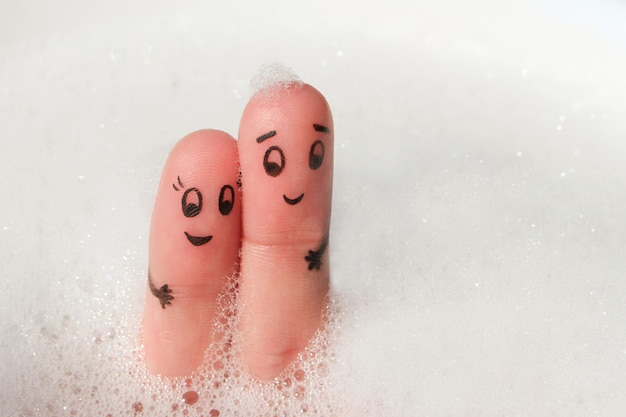 Finger art of happy couple bathe in bath with foam. Premium Photo