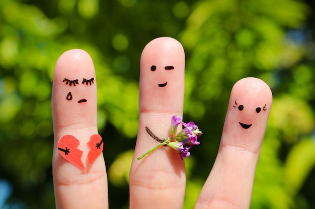 Finger art of people. man flirts with woman. other girl is holding broken heart Premium Photo