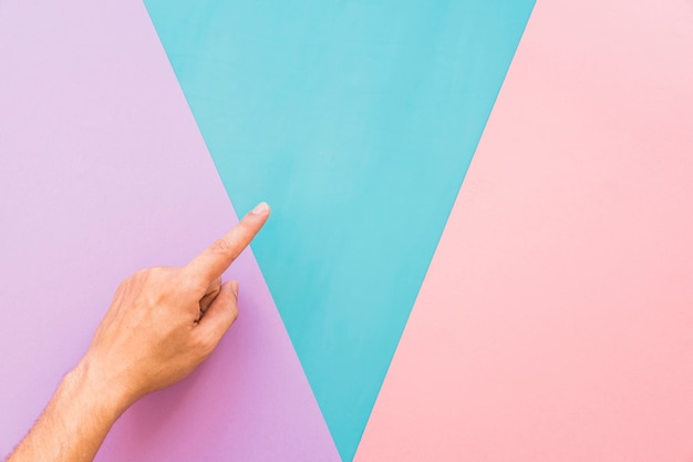 Finger above background with triangular shapes Free Photo