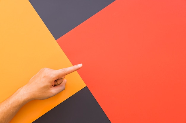 Finger pointing above geometric background Free Photo
