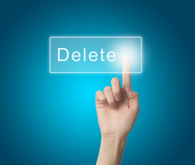 Finger pressing a delete key Free Photo