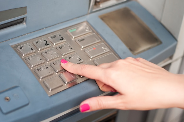 Finger pressing password number on atm machine Free Photo