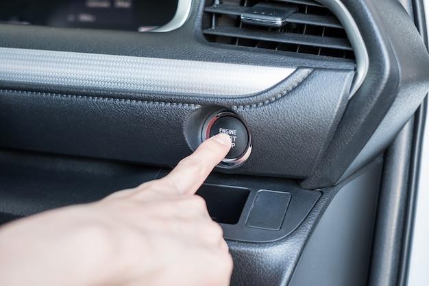 Finger pressing start engine car on control panel Premium Photo