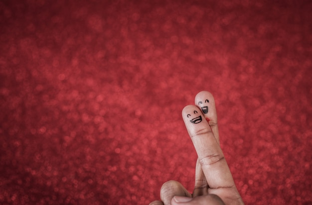 Finger with emotion on red background Free Photo