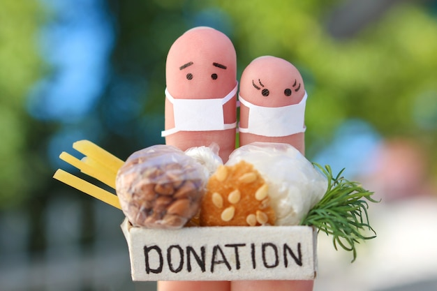 Fingers art of couple with face mask holding donation box with food Premium Photo