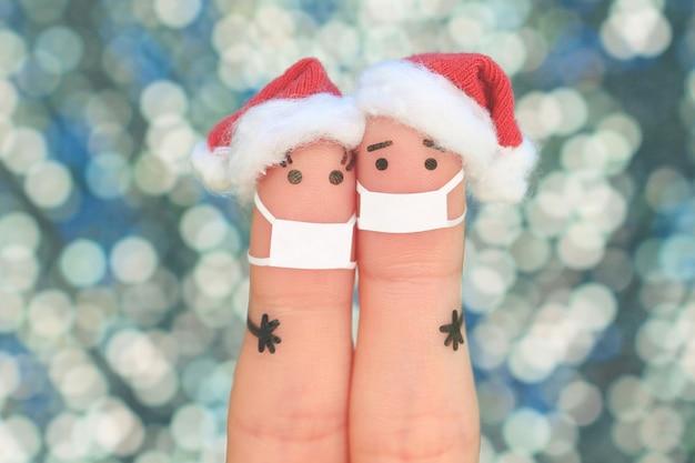 Искусство пальцами пары в медицинской маске от covid-2019 празднует рождество. Premium Фотографии