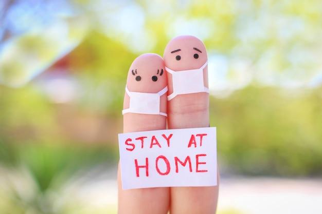 Пальцы искусство пары с маской сидит в карантине дома. люди держат плакаты дома, чтобы защитить себя от covid-2019. Premium Фотографии
