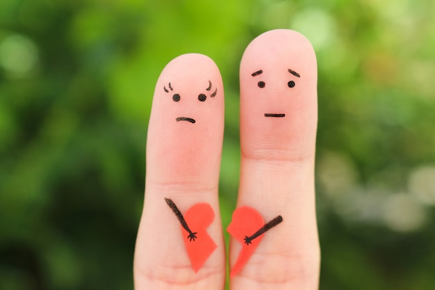 Fingers art of sad couple. woman and man holding broken heart. Premium Photo