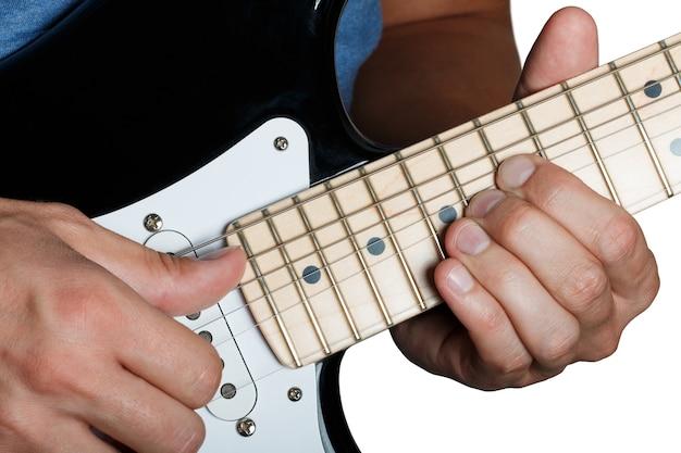Пальцы сгибают струны на кленовом грифе крупным планом, изолированном на белом Premium Фотографии