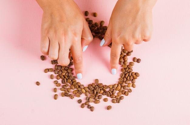 커피 콩의 심장 갭을 만드는 손가락 무료 사진