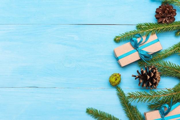 水色の背景に円錐形のモミの枝とコピースペースのギフト。 Premium写真