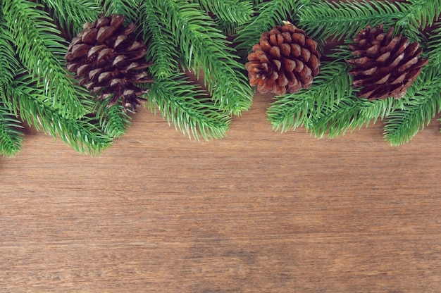 Fir tree branches and pine cones with decoration on a wooden board Premium Photo