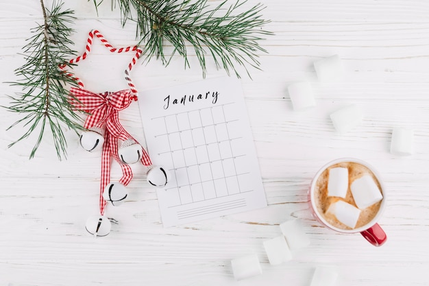 Fir tree branches with calendar and jingle bells Free Photo