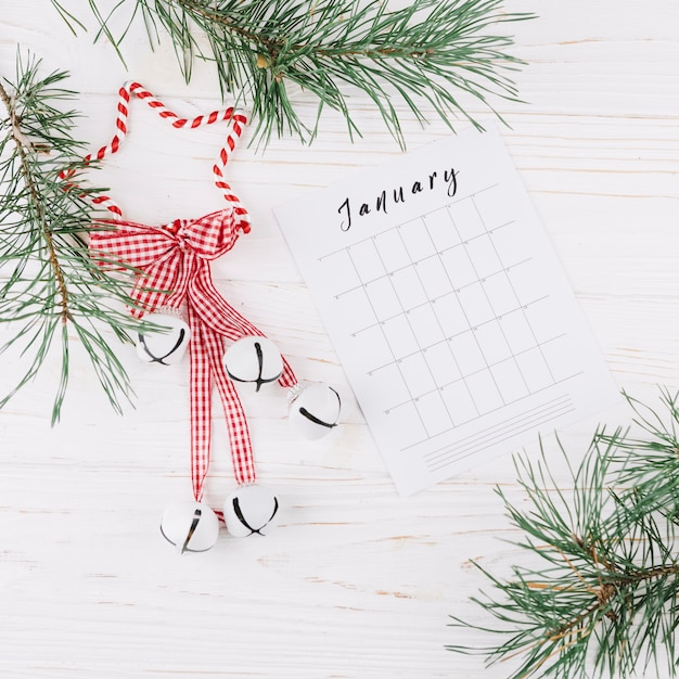 Fir tree branches with calendar on table Free Photo