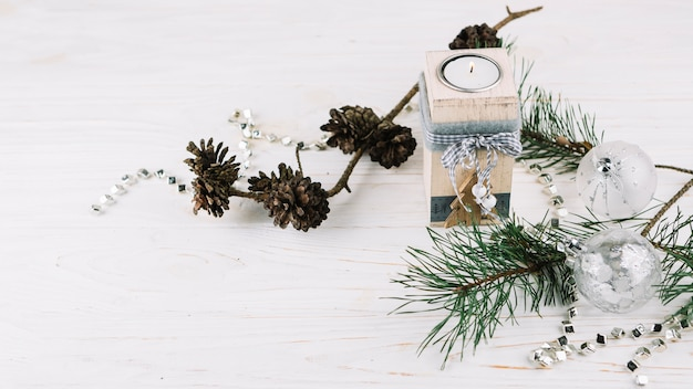 Fir tree branches with candle in candlestick Free Photo