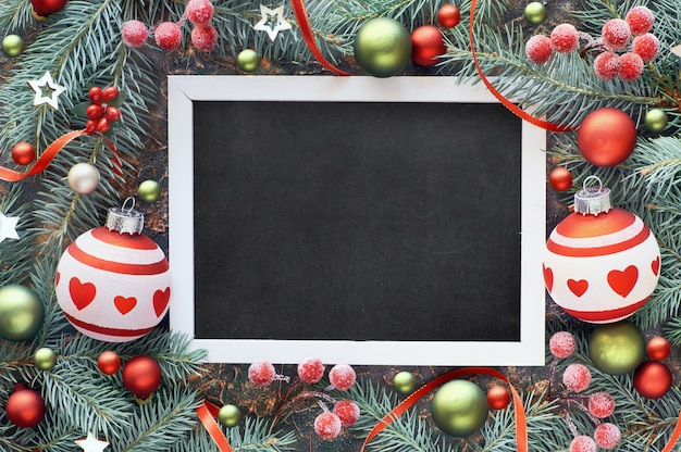 Fir twig decorated with baubles, berries and stars, black-board Premium Photo
