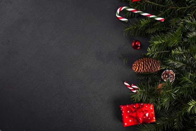 Fir twigs near candy canes and gift box Free Photo