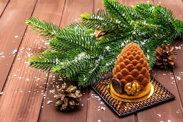 モミの枝とクリスマスfirコーンの形をしたお祝いデザート Premium写真