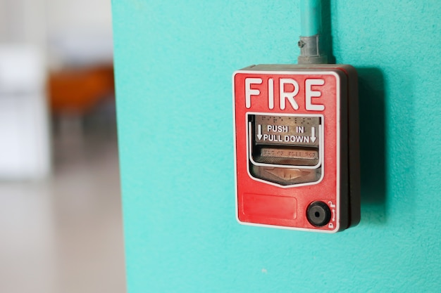 Fire alarm switch on the green wall in factory. Premium Photo