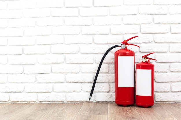 Fire extinguisher near white wall, ready for use Premium Photo