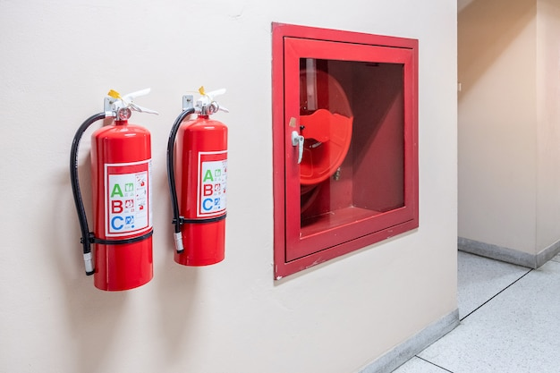 Fire extinguisher system on the wall background, powerful emergency equipment for industrial Premium Photo