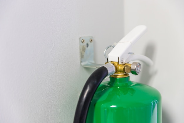 Fire extinguisher with green color, hang on the white wall. Premium Photo
