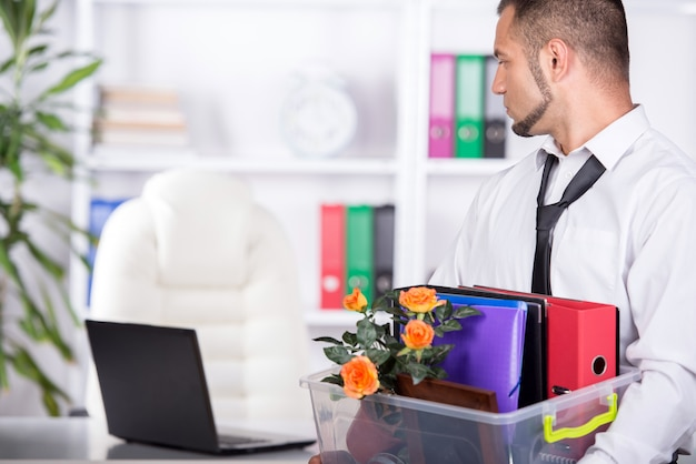 Fired businessman is packing his bags and leaving office. Premium Photo