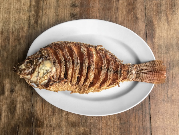 Fired tilapia fish dish on wood table background. Premium Photo