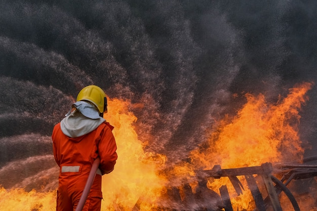 Firefighter are using water in fire fighting operation Premium Photo