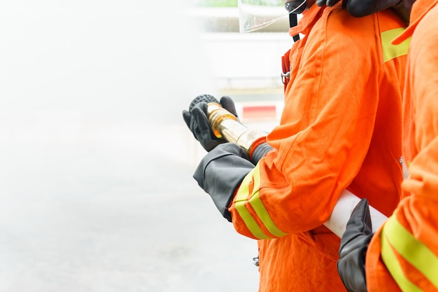 Firefighter using extinguisher and water from hose for fire fighting Premium Photo