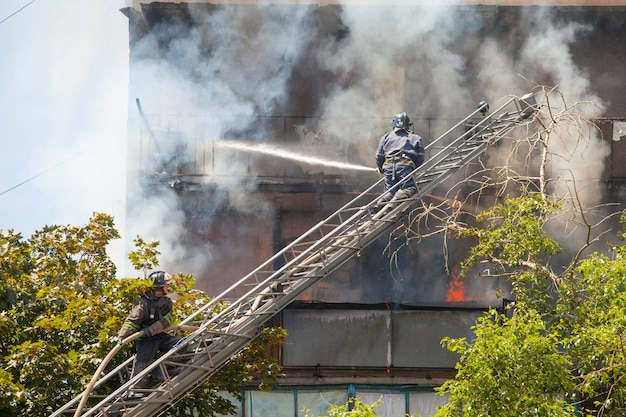 Firefighters extinguish a fire in a high-rise residential building. Premium Photo