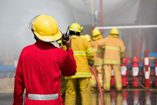 Firefighters spray water in fire extinguishers caused by explosive gas Premium Photo