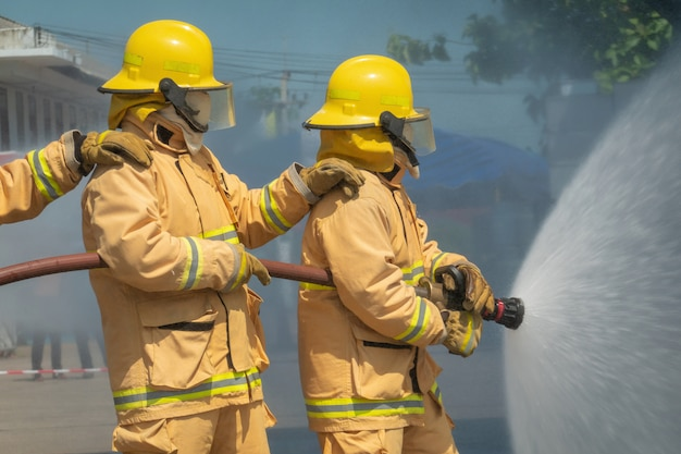 Firefighters training with water hose Premium Photo