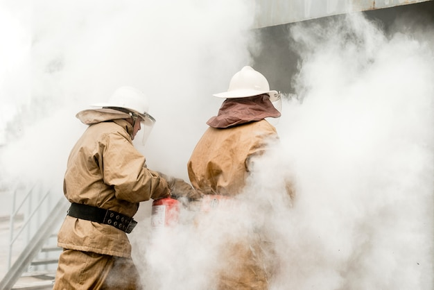 Firefighters use extinguishers on a training how to stop fire in a dangerous mission Premium Photo