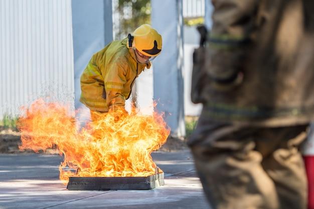 Показ пожарного использует огнетушитель на пожарном гидранте тренировки с белым дымом. концепция гигиены труда и техники безопасности. Premium Фотографии