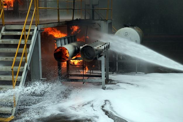 消防士の訓練スプレー水カーテンが火を止めるのを助けました。 Premium写真