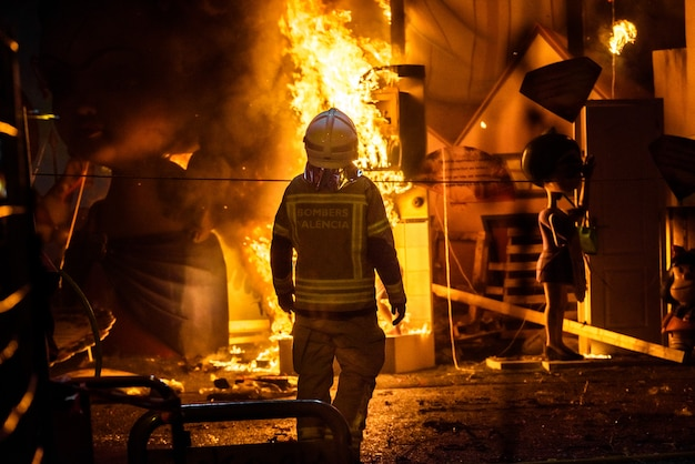 Firemen around a bonfire caused by a falla valenciana controlling the flames of the fire. Premium Photo