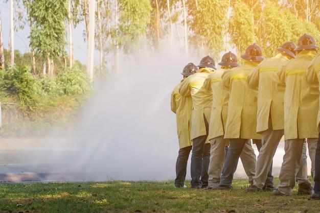 消火のため消火器とホースからの水を使っている消防士 Premium写真