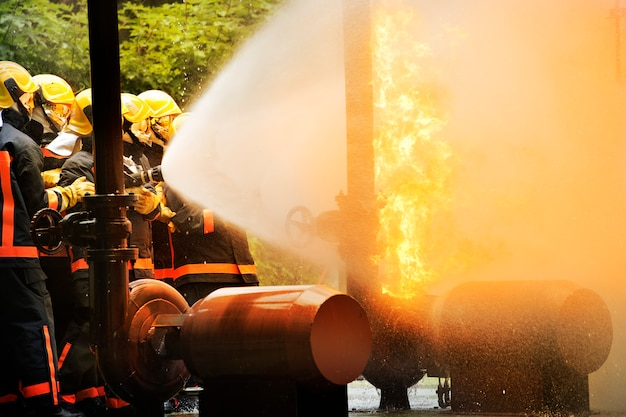 Firemen using extinguisher and water for fighter fire during firefight training. Premium Photo