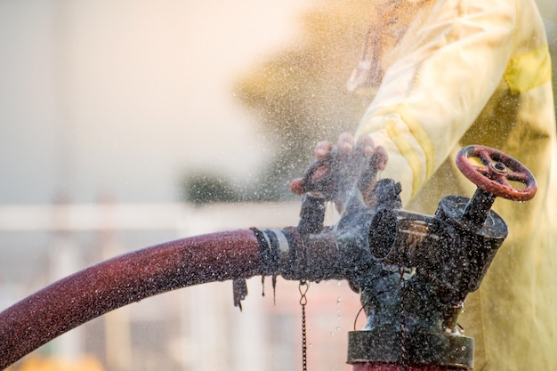Firemen using water from hose for fire fighting at fire fight training of insurance group. firefighter wearing a fire suit for safety under the danger training case. Premium Photo